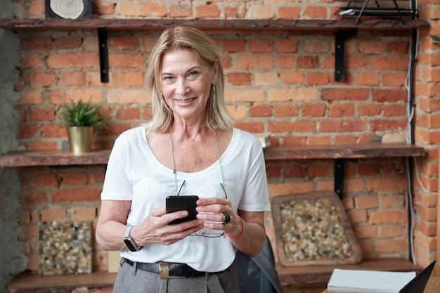 Portret uśmiechnięta nowoczesna dojrzała kobieta menedżer z blond włosy surfowania w sieci na smartfonie