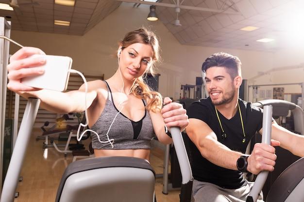 Portret uśmiechnięta para rozmawia selfie na siłowni. młody mężczyzna i kobieta w odzieży sportowej biorąc selfie w klubie fitness