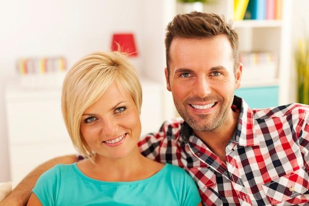 Portret uśmiechnięta para w salonie