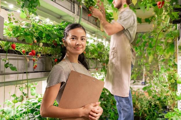 Portret uśmiechnięta pewna, młoda pracownica małej szklarni stojącej na półce roślin i trzymając schowek