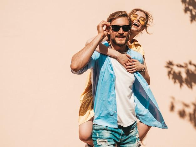 Portret uśmiechnięta piękna dziewczyna i jej przystojny chłopak. kobieta w casual letnią sukienkę i mężczyzna w dżinsach. szczęśliwa, wesoła rodzina. kobieta zabawy na ulicy w pobliżu ściany