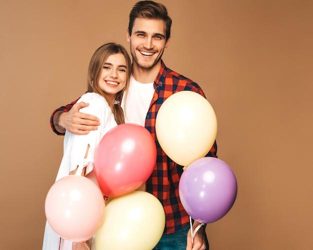 Portret uśmiechnięta piękna dziewczyna i jej przystojny chłopak trzyma bukiet kolorowych balonów i śmiejąc się. szczęśliwa para zakochanych. wszystkiego najlepszego