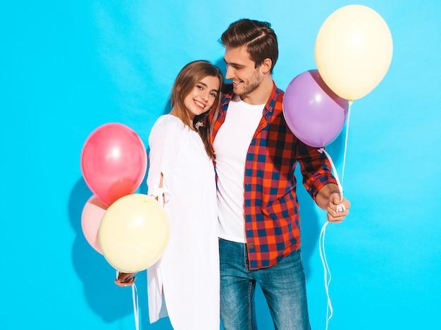 Portret uśmiechnięta piękna dziewczyna i jej przystojny chłopak trzyma bukiet kolorowych balonów i śmiejąc się. wszystkiego najlepszego