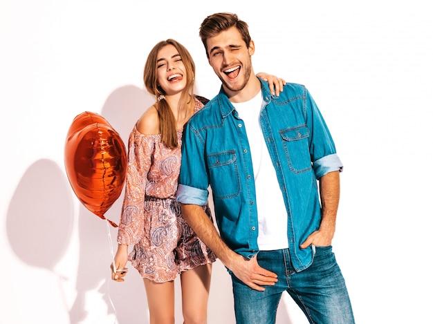Portret uśmiechnięta piękna dziewczyna i jej przystojny chłopak trzymając balony w kształcie serca i śmiejąc się. miłość. szczęśliwych walentynek.