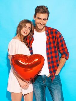 Portret uśmiechnięta piękna dziewczyna i jej przystojny chłopak trzymając balony w kształcie serca i śmiejąc się. szczęśliwa para zakochanych. szczęśliwych walentynek. pozowanie
