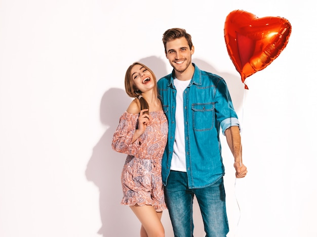 Portret uśmiechnięta piękna dziewczyna i jej przystojny chłopak trzymając balony w kształcie serca i śmiejąc się. szczęśliwa para zakochanych. szczęśliwych walentynek
