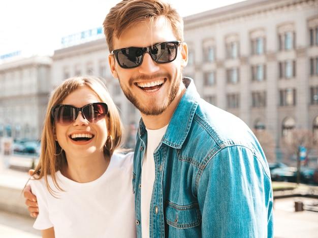 Portret uśmiechnięta piękna dziewczyna i jej przystojny chłopak w przypadkowych letnich ubraniach i okularach przeciwsłonecznych. . tulenie