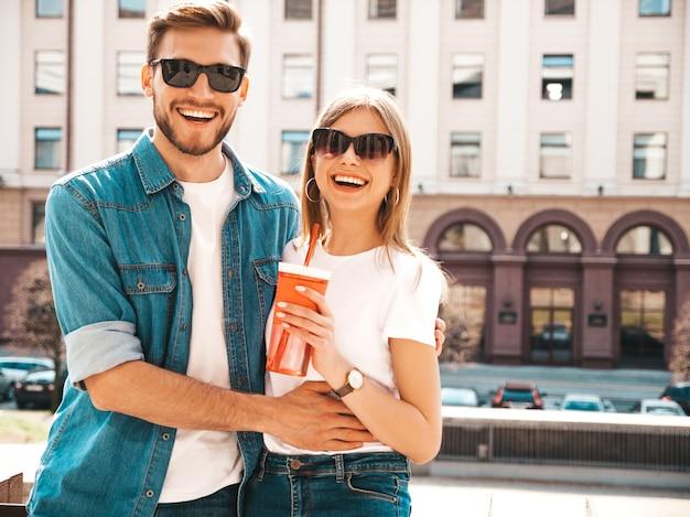 Portret uśmiechnięta piękna dziewczyna i jej przystojny chłopak w przypadkowych letnich ubraniach. . kobieta z butelką wody i słomy
