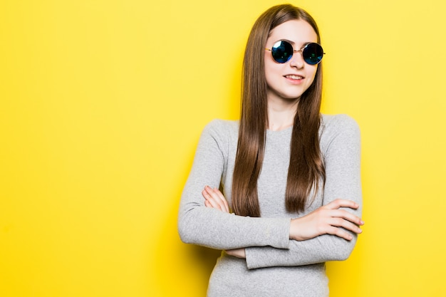Portret uśmiechnięta piękna kobieta w okularach przeciwsłonecznych i sukni przeciw kolor żółty ścianie