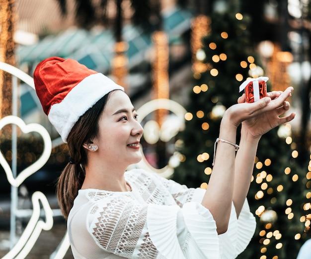 Portret uśmiechnięta piękna młoda azjatycka kobieta z prezentem na świątecznym jarmarku bożonarodzeniowy