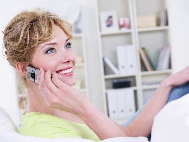 Portret uśmiechnięta piękna wesoła kobieta z mobilnym mówieniem - w pomieszczeniu