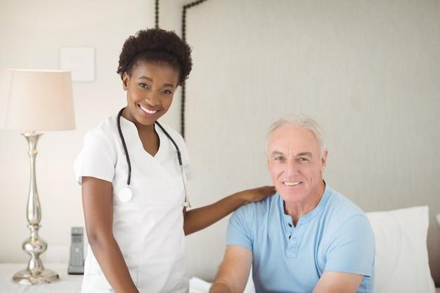 Portret uśmiechnięta pielęgniarka i starszy mężczyzna w sypialni
