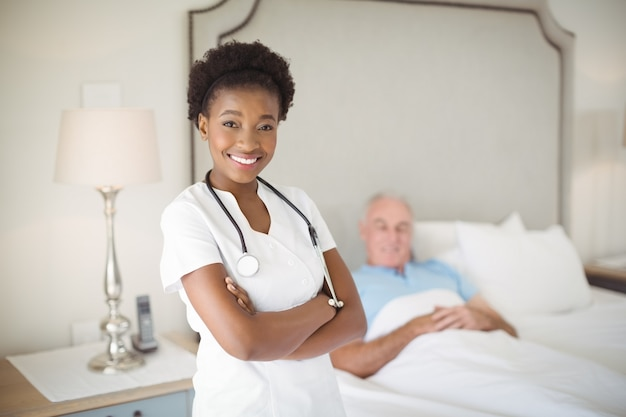 Portret uśmiechnięta pielęgniarka stojąca z rękami skrzyżowanymi, podczas gdy starszy mężczyzna leży na łóżku