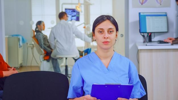 Portret uśmiechnięta pielęgniarka w gabinecie stomatologicznym, podczas gdy lekarz pracuje z pacjentem w tle. asystent stomatologa patrząc na kamerę internetową, siedząc na krześle w klinice stomatologicznej.