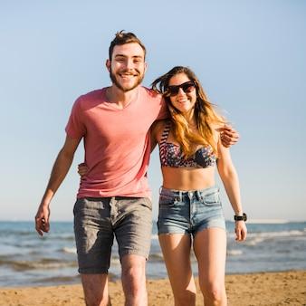 Portret uśmiechnięta potomstwo para cieszy się wakacje przy plażą