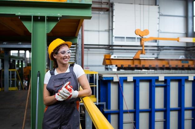 Portret uśmiechnięta pracownica fabryki stojącej w przemysłowej hali produkcyjnej