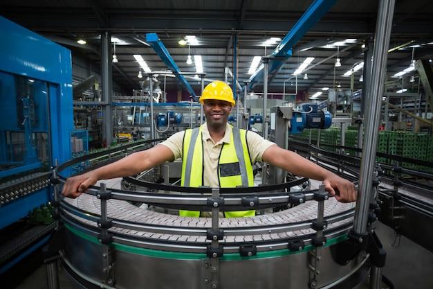 Portret uśmiechnięta pracownik fabryczny pozycja blisko konwejeru paska w fabryce