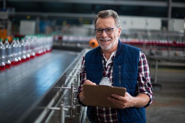 Portret uśmiechnięta pracownik fabryczny pozycja z schowkiem