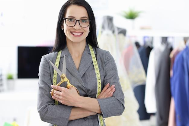 Portret uśmiechnięta projektantka mody kobieta z nożyczkami w dłoniach.