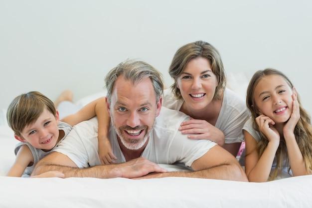 Portret uśmiechnięta rodzina leżąc na łóżku w sypialni