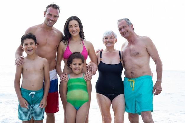 Portret uśmiechnięta rodzina stojąc na plaży