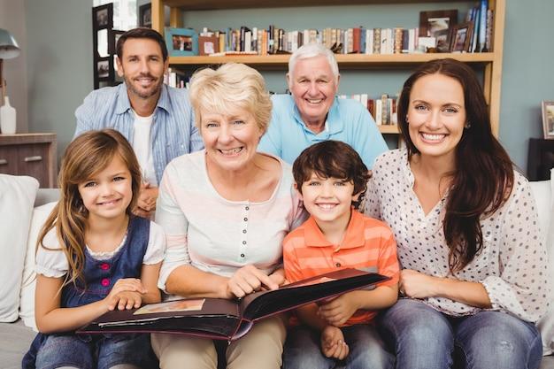 Portret uśmiechnięta rodzina z dziadkami trzyma album fotograficznego
