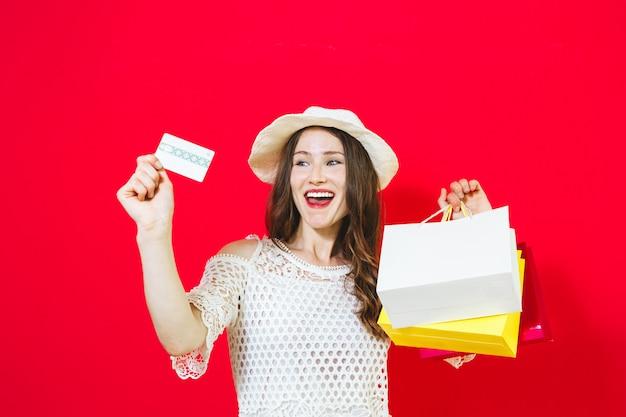 Portret uśmiechnięta rozochocona dziewczyny mienia torba na zakupy i seans kredytowa karta nad czerwienią