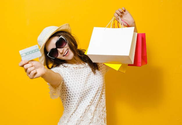 Portret uśmiechnięta rozochocona dziewczyny mienia torba na zakupy i seans kredytowa karta nad kolorem żółtym