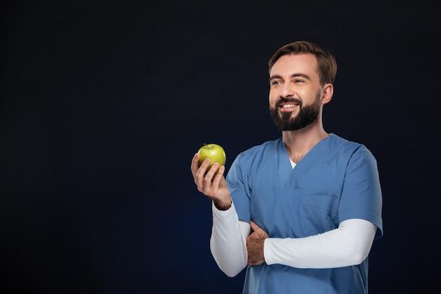 Portret uśmiechnięta samiec lekarka ubierał w mundurze