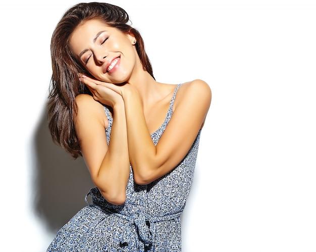 Portret uśmiechnięta śliczna modniś kobieta w przypadkowych letnich ubraniach bez makeup na biel ścianie
