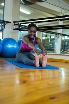 Portret uśmiechnięta sprawna kobieta robi ćwiczenia rozciągające na macie