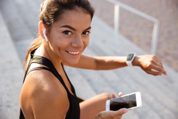 Portret uśmiechnięta sprawności fizycznej kobieta w słuchawkach