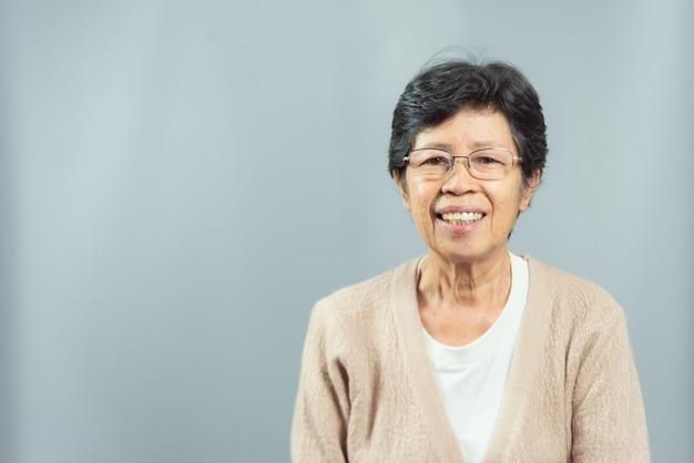 Portret uśmiechnięta stara kobieta szczęśliwa na szarość