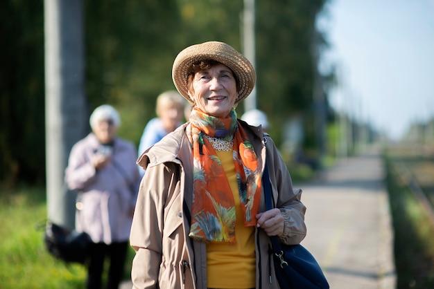 Portret uśmiechnięta starsza kobieta ubrana w letni kapelusz podróży