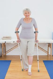 Portret uśmiechnięta starsza kobieta z szczudłami w szpitalnym gym