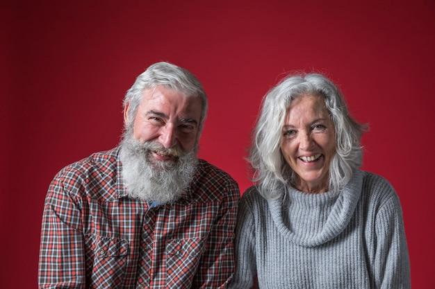 Portret uśmiechnięta starsza para z szarym włosy przeciw czerwonemu tłu