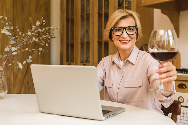 Portret uśmiechnięta starsza starsza kobieta trzyma kieliszek wina podczas korzystania z laptopa na stole w kuchni. niezależny pracujący w koncepcji domu.