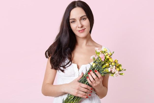 Portret uśmiechnięta szczera młoda modelka stojący na białym tle nad jasnoróżowym, trzymając w rękach kolorowe wiosenne kwiaty