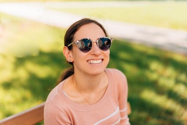 Portret uśmiechnięta szczęśliwa kobieta na zewnątrz w parku podczas zachodu słońca