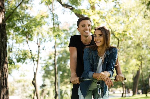 Portret uśmiechnięta szczęśliwa para jedzie na bicyklu