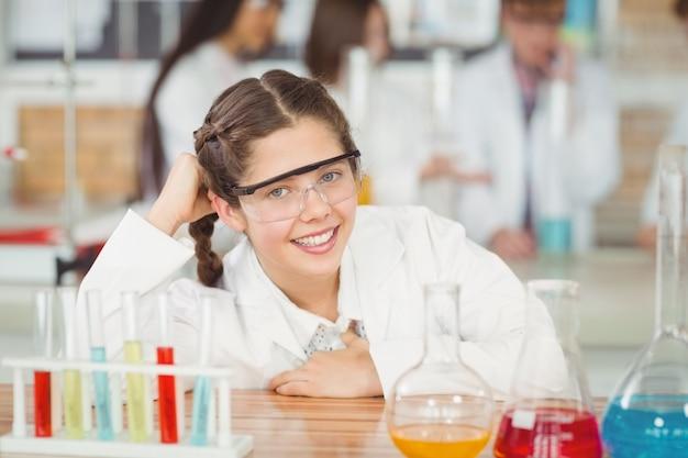Portret uśmiechnięta uczennica opierając się na stole w laboratorium