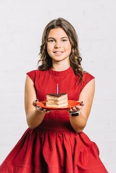 Portret uśmiechnięta urodzinowa dziewczyna trzyma plasterek tort na talerzu z iluminującą świeczką