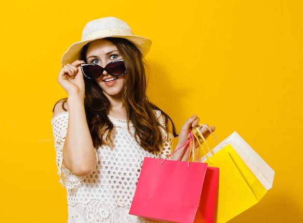 Portret uśmiechnięta wesoła dziewczyna gospodarstwa torby na zakupy na żółty