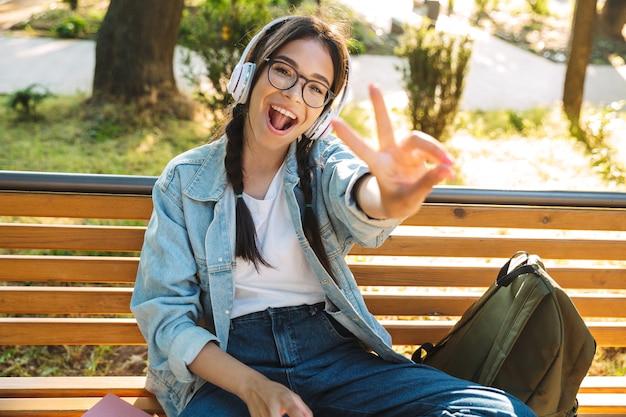 Portret uśmiechnięta wesoła śliczna młoda studentka w okularach, siedząca na ławce na świeżym powietrzu w parku przyrody, słuchając muzyki w słuchawkach pokazując gest pokoju.