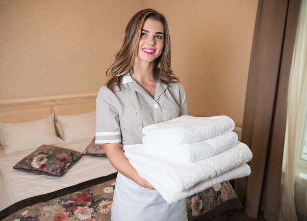 Portret uśmiechnięta żeńska gosposia trzyma brogującego miękcy ręczniki w pokoju hotelowym