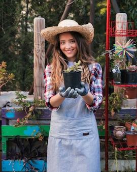 Portret uśmiechnięta żeńska ogrodniczka jest ubranym kapelusz pokazuje kaktusowej rośliny w ogródzie