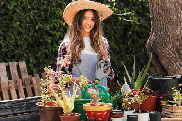 Portret uśmiechnięta żeńska ogrodniczki pozycja w ogródzie
