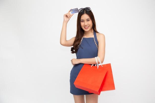 Portret uśmiechnięte azjatykcie kobiety trzyma kredytową kartę i czerwonego torba na zakupy odizolowywającymi nad biel ścianą, młodej kobiety szczęśliwy uczucie kupującego pojęcie