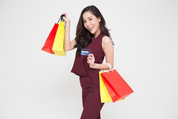 Portret uśmiechnięte azjatykcie kobiety trzyma kredytową kartę i torba na zakupy odizolowywającymi nad biel ścianą, młodej kobiety szczęśliwy uczucie kupującego pojęcie