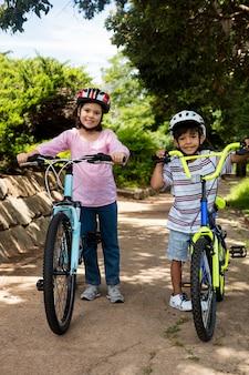 Portret uśmiechnięte dzieci stojąc z rowerem w parku